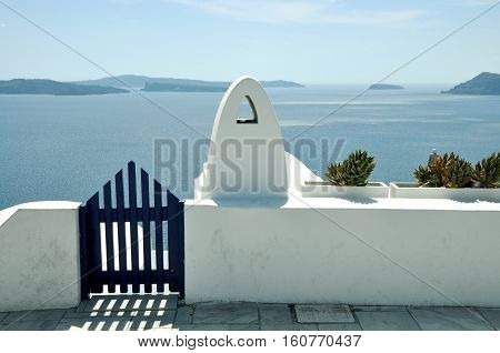 blue gate wicket and white fence. Mediterranean sea and Santorini caldera  on the background. concept of leasure, freedom, luxury