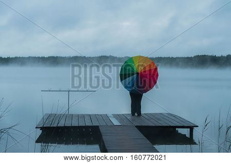 The girl in the fog on the pier with a rainbow umbrella looking into the distance view from the back