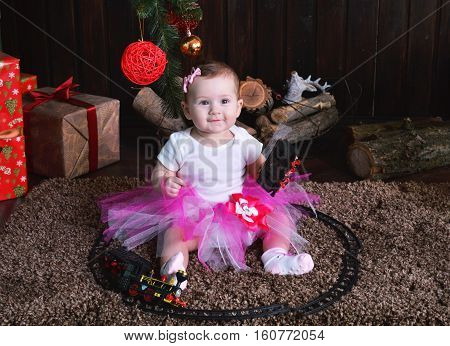 Cute little girl sitting under the Christmas tree. Baby holding a toy train in her hands