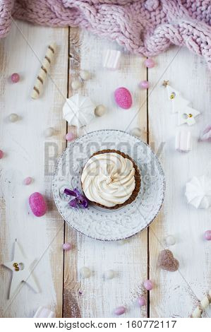Christmas candy background. Cupcake with  cream on plate, flat lay.