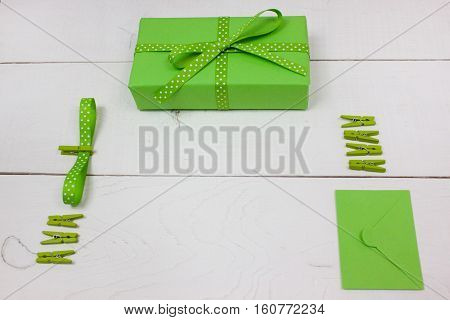 Green gift with polka dot ribbon and envelope on white wood background