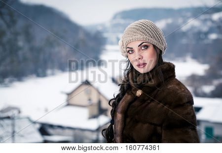 Portrait of young girl in the winter. The girl saunters in the park.