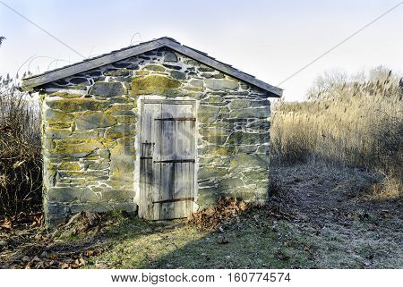 Bristol Rhode Island USA - January 25 2008: Small stone building at edge of marsh below Coggeshall Farm in Bristol Rhode Island