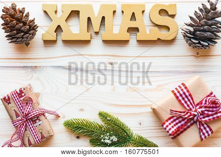 Christmas decoration with fir tree branchword xmaspine cones and gifts on wooden background with copyspace top view flat lay.