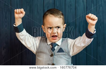 Portrait of kid boy wears elegant suit with tie showing hands up before blue wood wall
