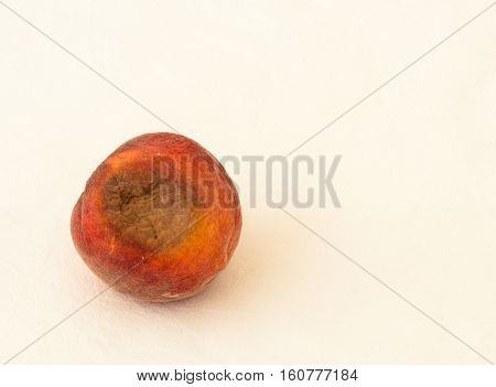 Spoiled And Moldy Peach On A White Background