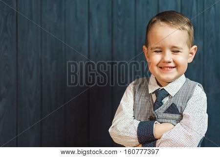 Portrait of smiling kid boy wears elegant suit with tie before blue wood wall