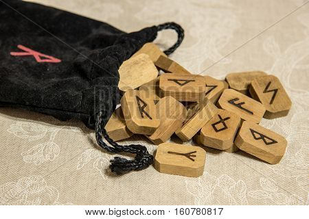 Wooden runes with black bag. Esoteric subjects.