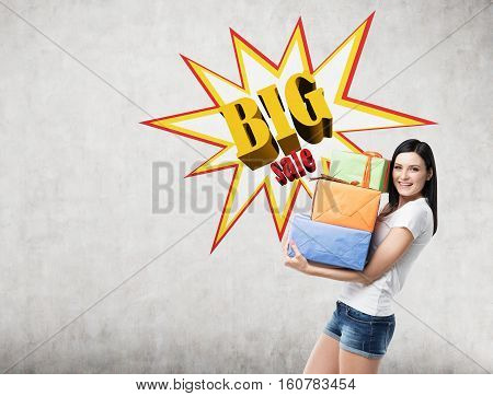 Smiling woman wearing shorts and a T-shirt and holding presents near a concrete wall with a big sale poster on it. Mock up