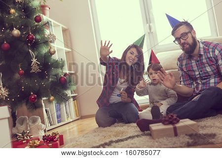 Beautiful young family having fun together for Christmas holidays sitting on a living room floor next to a nicely decorated Christmas tree smiling and waving. Focus on the baby girl