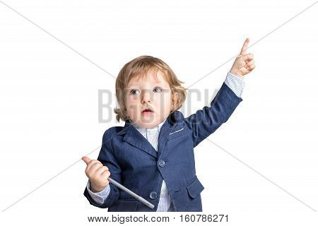 Isolated portrait of a baby boy in a suit holding a pen and pointing upwards. Concept of a future businessman. Mock up