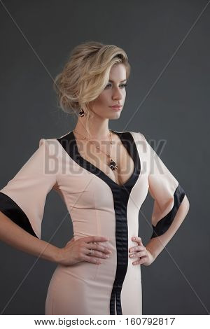 Fashion model with blond hair. Young attractive woman, grey background.