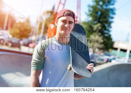 Cool urban skateboarder posing outdoors in summer day