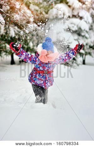 little Caucasian girl tossing snow in rainbow