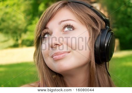 Portrait of the beautiful girl listening to music in ear-phones in park