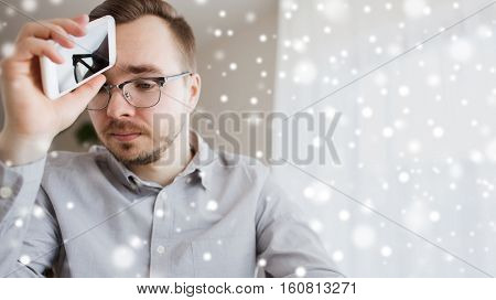 business, stress, communication, technology and people concept - businessman or creative male worker with smartphone at home or office over snow
