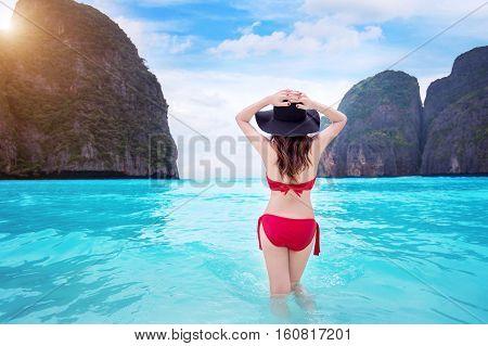 Woman in red bikini at tropical beach.