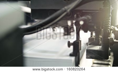 Printed sheets of paper are served in the printing press. Offset printing, CMYK, close up, backlight