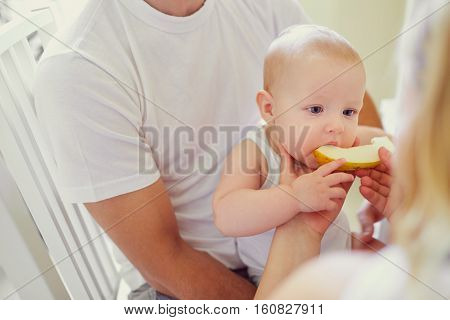 Feeding the children fruit. Parents feed their baby melon.