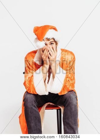 Playful man shy handsome young male model in red santa claus hat and suit for Christmas or new year laughs timid hiding face with hands isolated on white
