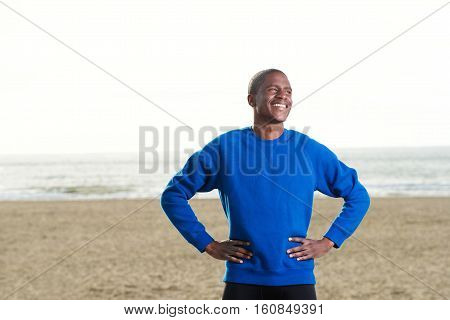 Handsome African Guy Standing At The Beach In Blue Sweatshirt