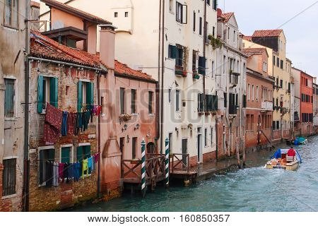 Channel street in old Venice, Italy. Wet buildings by the channel embankment. Italy travel photo. Historical part of Venice old town image
