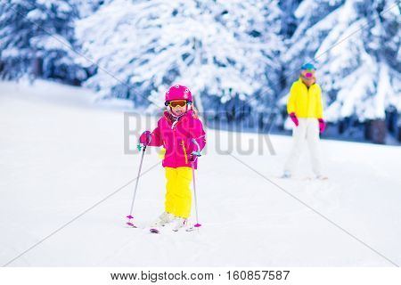 Family ski vacation. Group of skiers in Swiss Alps mountains. Mother and child skiing in winter. Parents teach kids alpine downhill skiing. Ski gear and wear safe helmets.