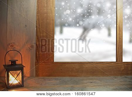 Lantern next to a window with wintery scenery outdoors