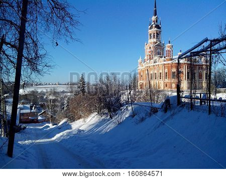 Russia; Mozhaisk; Moscow region.The descent on the Borodinskaya street by Novo-Nikolsky Cathedral. Mozhajskij Kremlin.Sunny winter's day.Snowy road.