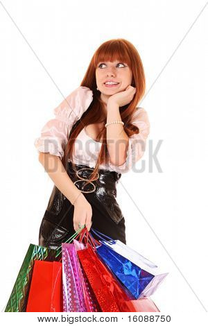 Beautiful, young, redhead woman with color  shopping bags in her hand.  Isolated on white background.