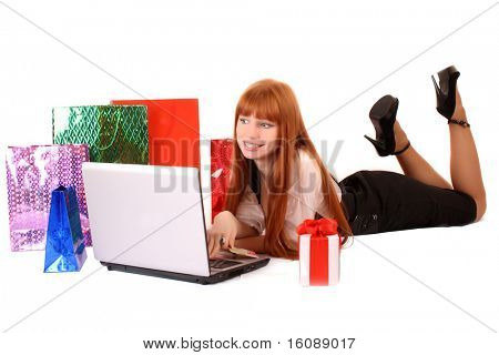 Beautiful, young, redhead woman with color shopping bags shopping over internet. On white background.