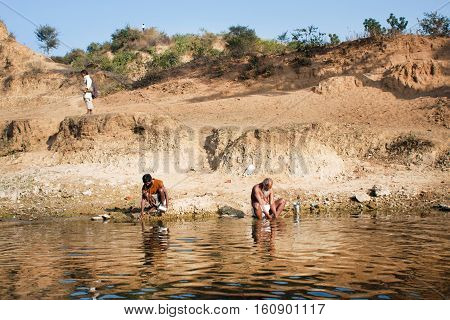 CHITRAKOOT, INDIA - DEC 28, 2012: Morning washing of poor men on the river bank in the rural landscape on December 28, 2012. Population of Chitrakoot is 22294. By the legend Lord Rama lived here