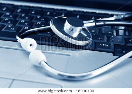 Doctor stethoscope on the laptop keyboard. Image in blue tone.