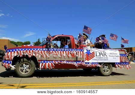 MANDAN, NORTH DAKOTA, July 3, 2016: The 4th of July Rodeo Days  3 day celebration includes the rodeo, Art in the Park, and downtown parade where a patriotic decorated pickup transports Daughters of the American Revolution.