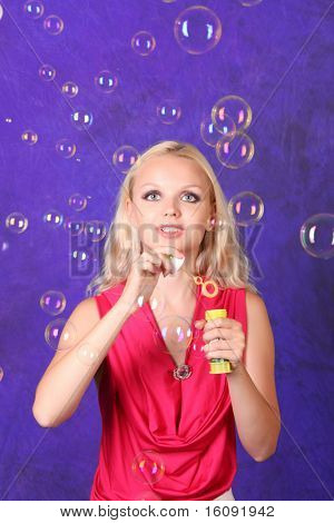 Beautiful young woman blowing soap bubbles on blue