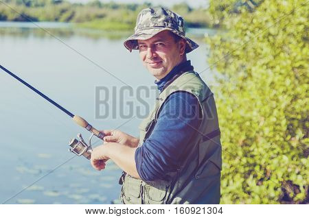 man in hot day successfully catches fish on a reservoir in the summer a spinning