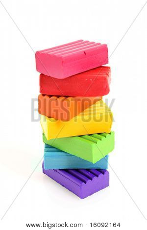 Children bright multicoloured plasticine in the column  isolated on white