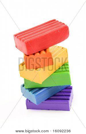 Children bright multicoloured plasticine in the column  isolated on white