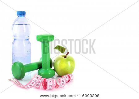 Dumbbells, green apple, measuring tape and a bottle of water isolaeted on white