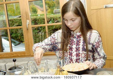 A beautiful pre teen girl in the kitchen