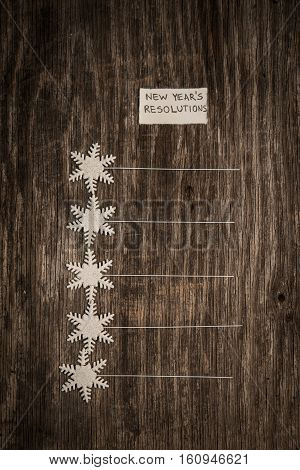 New Year's Resolutions On A Blank List On Wooden Background