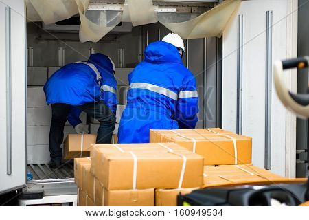 Manual worker working with package boxes for transport by pickup at gates for goods in loading area from warehouse to be processed export to customer