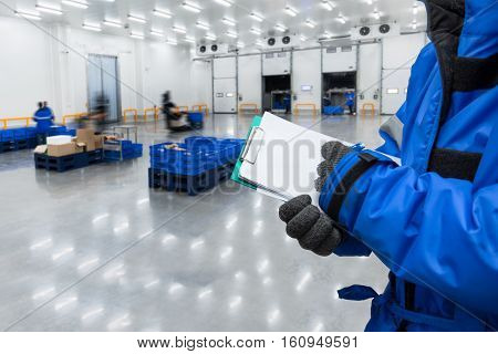 Hand of worker with clipboard checking ready meals goods in the warehouse. Import and export management system for customer service concept.