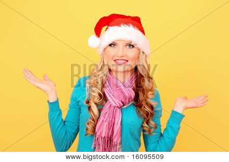 Beautiful christmas woman thinking in santa hat on yellow background