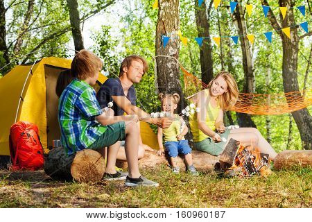 Happy active family roasting marshmallow on the sticks over campfire in summer