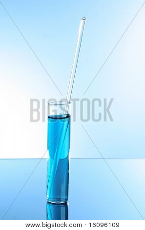 Test tube on blue background. With glass stick