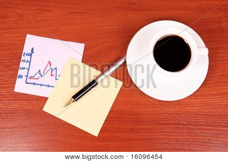 cup of coffee, a couple of stickers, chart and pen on table background