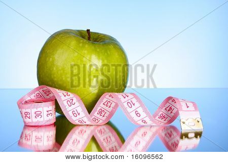 Fresh green tasty apple with measuring tape on blue background