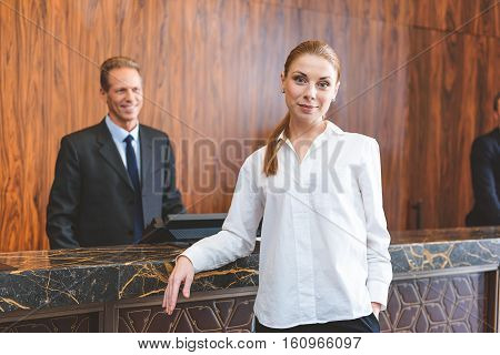 Waiting for porter. Smiling young woman standing near counter desk and looking at camera with hotel manager on background