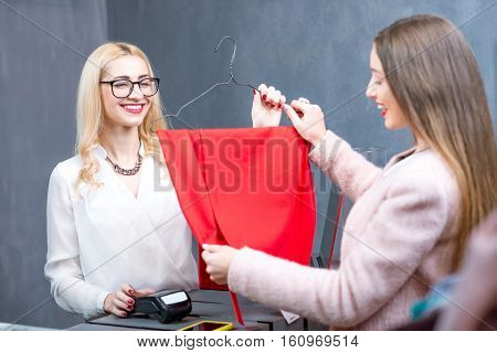 Happy woman buying red dress at the paydesk with cashier in the clothing store